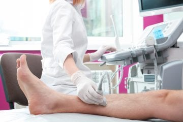Doctor conducting ultrasound examination of patient's leg in clinic, closeup